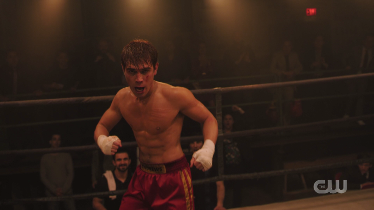 Topless Archie, with white tape around his hands and red satin shorts and blood all over his face, stands a little unsteadily in a boxing ring.