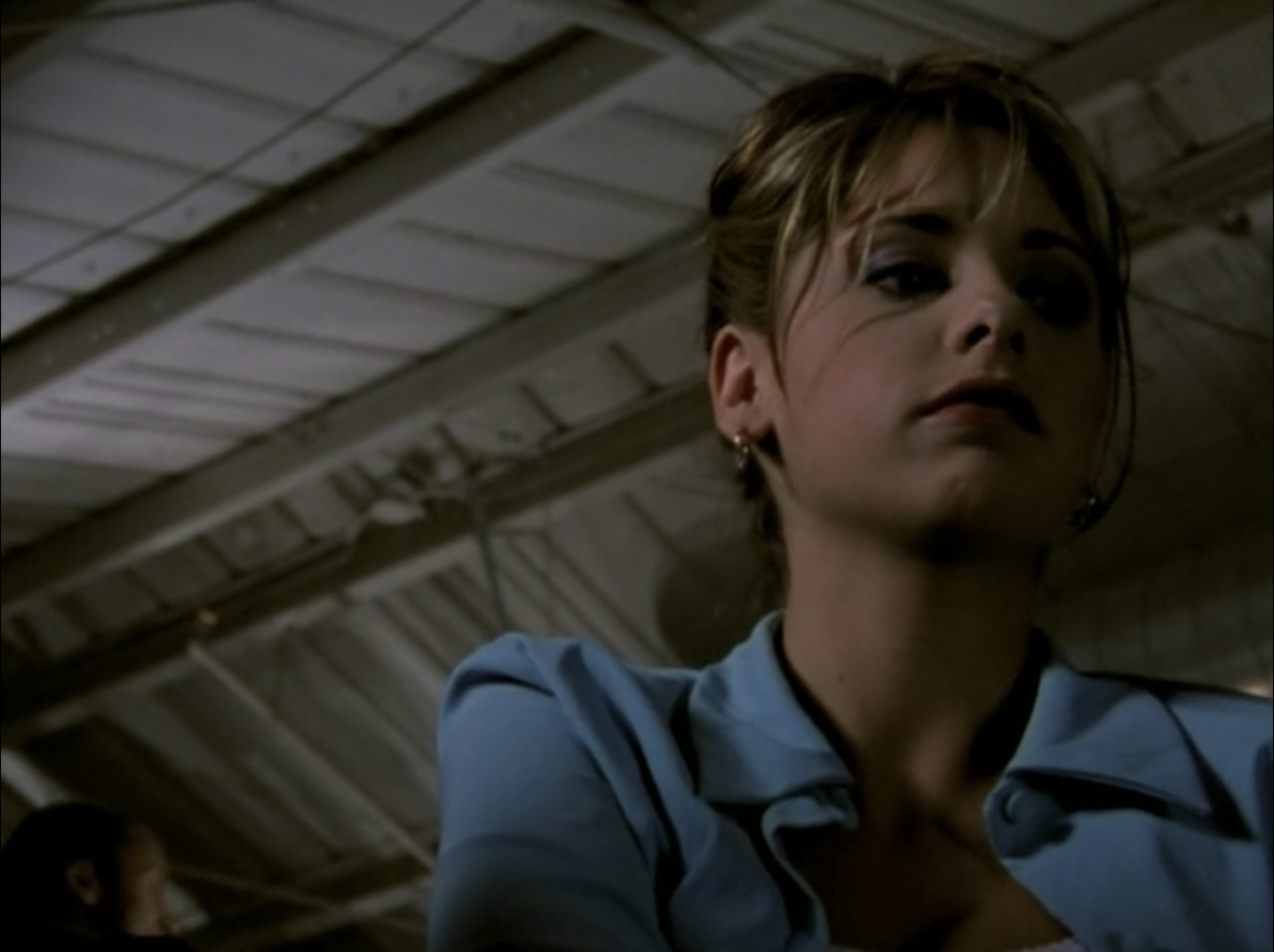 Buffy is seen in a darkened balcony, looking below her.