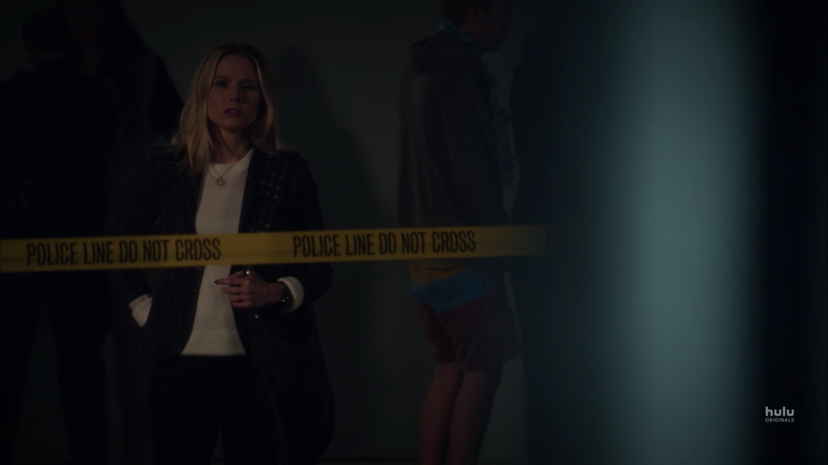 Veronica stands behind police tape, wearing a blazer and a white T-shirt, and looking intrigued by something.