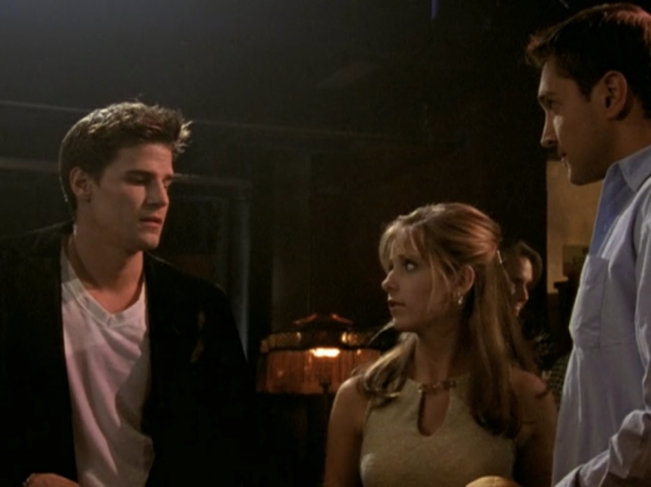 Angel, in a black jacket, looks sexily at Buffy, who looks nervously at him, while Owen stands next to Buffy.