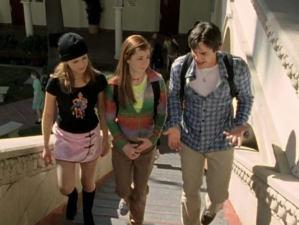 Xander (right), Willow (middle) and Buffy (left) walk up the stairs in bright sunlight. Buffy is wearing a black woolen cap, a black graphic T-shirt, a pink satin skirt with black contrast latches, and black knee-high boots.
