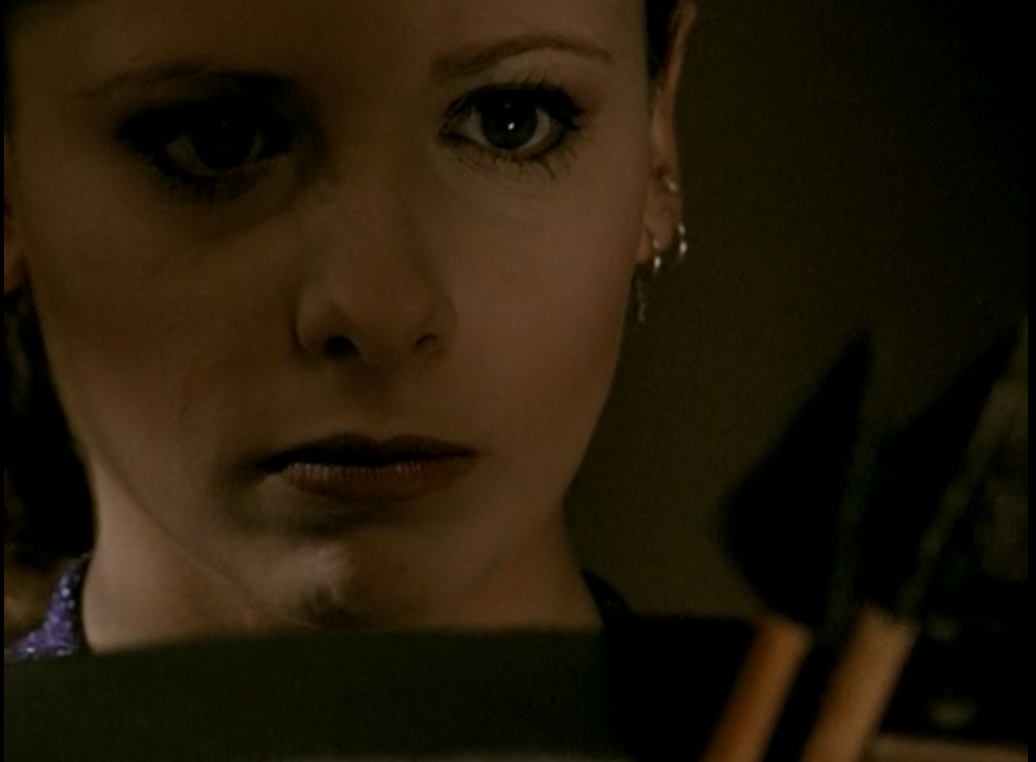 Buffy looks straight ahead with an intense expression, two arrowheads in front of her face.