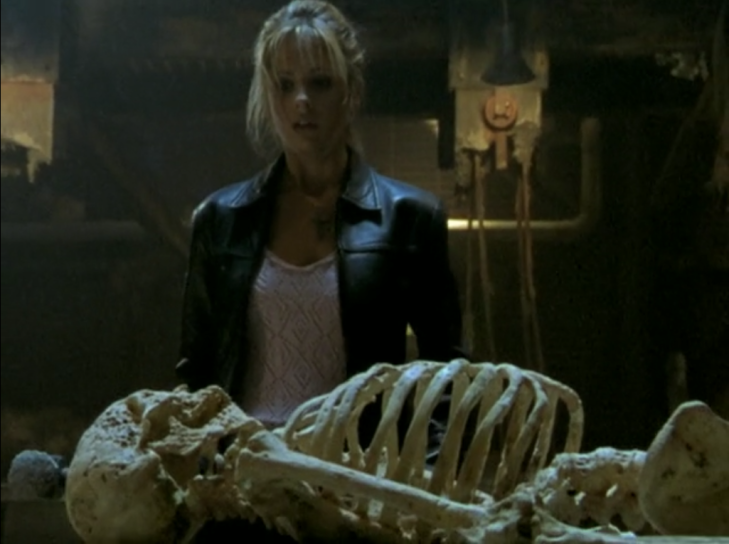 Buffy stands above a skeleton, holding a sledgehammer,