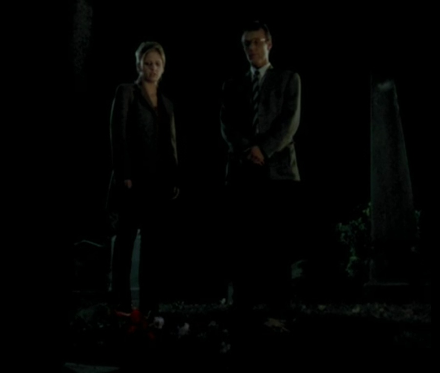 Buffy and Giles stand in the cemetery.