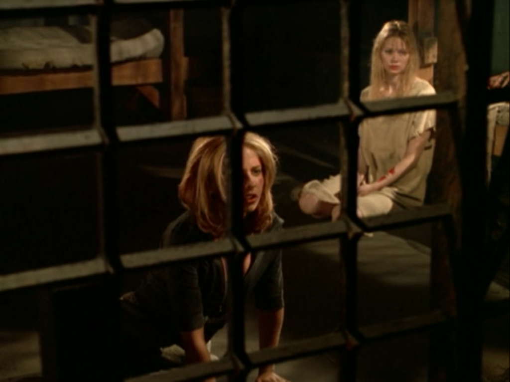 Buffy and another young woman sit in a jail cell