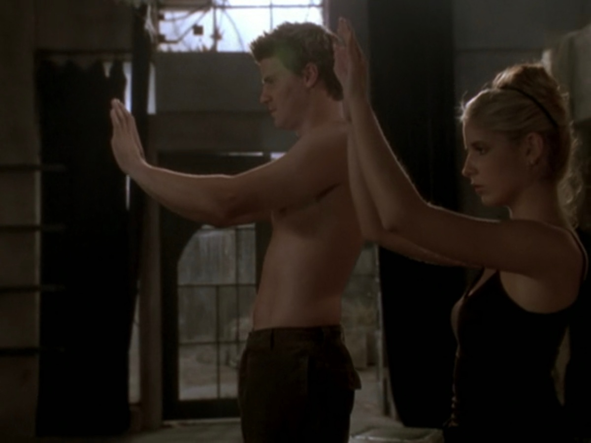 Buffy and Angel wear skimpy workout clothes and do a tai chi pose side by side, arms out in front of them.