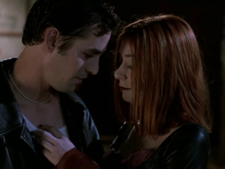 Willow and Xander, in vampire makeup and outfits, lean their heads close together with Willow's hand on Xander's chest.