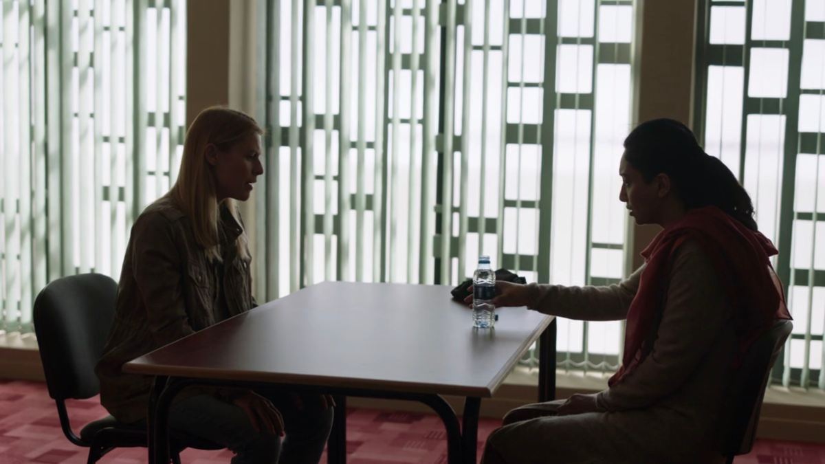 Carrie sits across an interrogation table from a woman in an unwrapped headscarf drinking from a water bottle.
