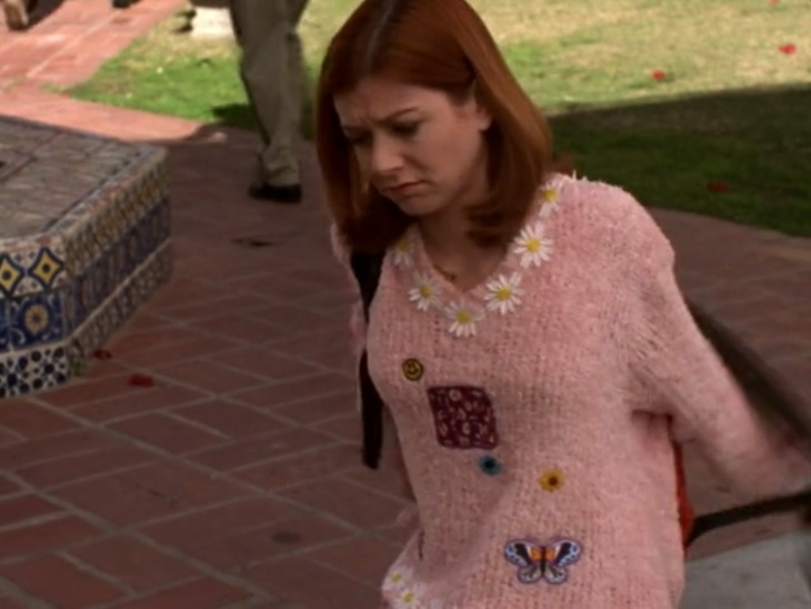 Willow kneels on the ground looking cranky. Wears a pink chenille sweater with daisies around the neck, a red square in the middle, a smiley face, two daisies, and a butterfly appliqued to it.