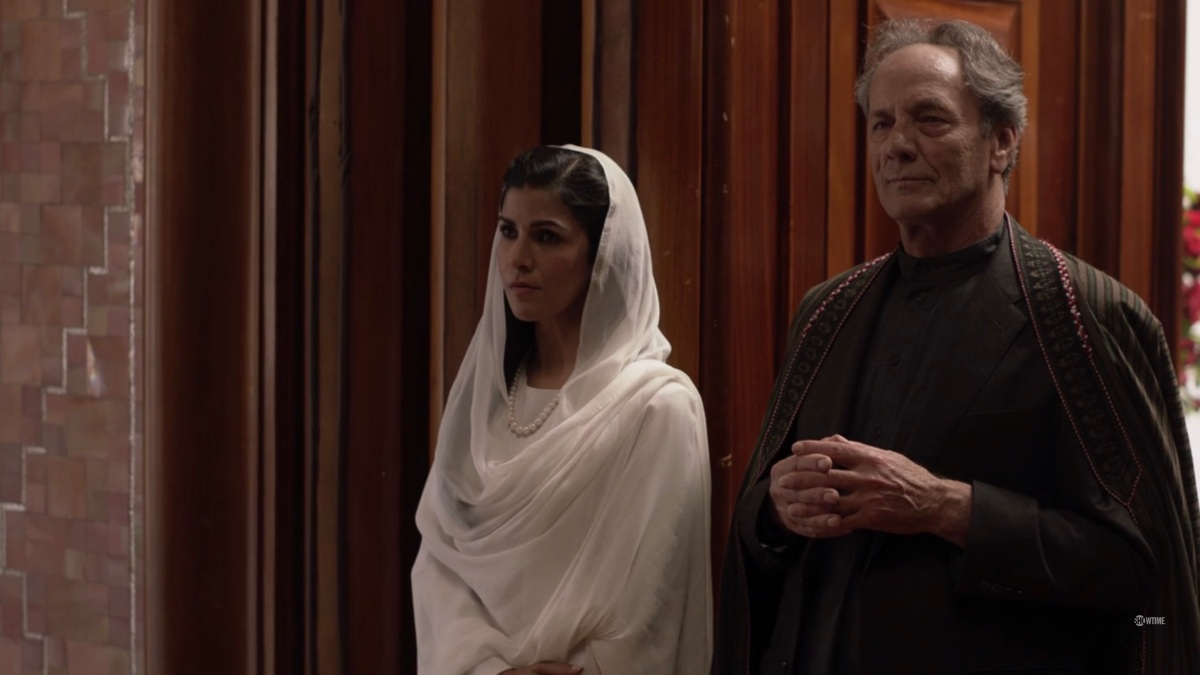 Tasneem, in a bright white outfit, and G'ulom stand in a corner looking cranky.