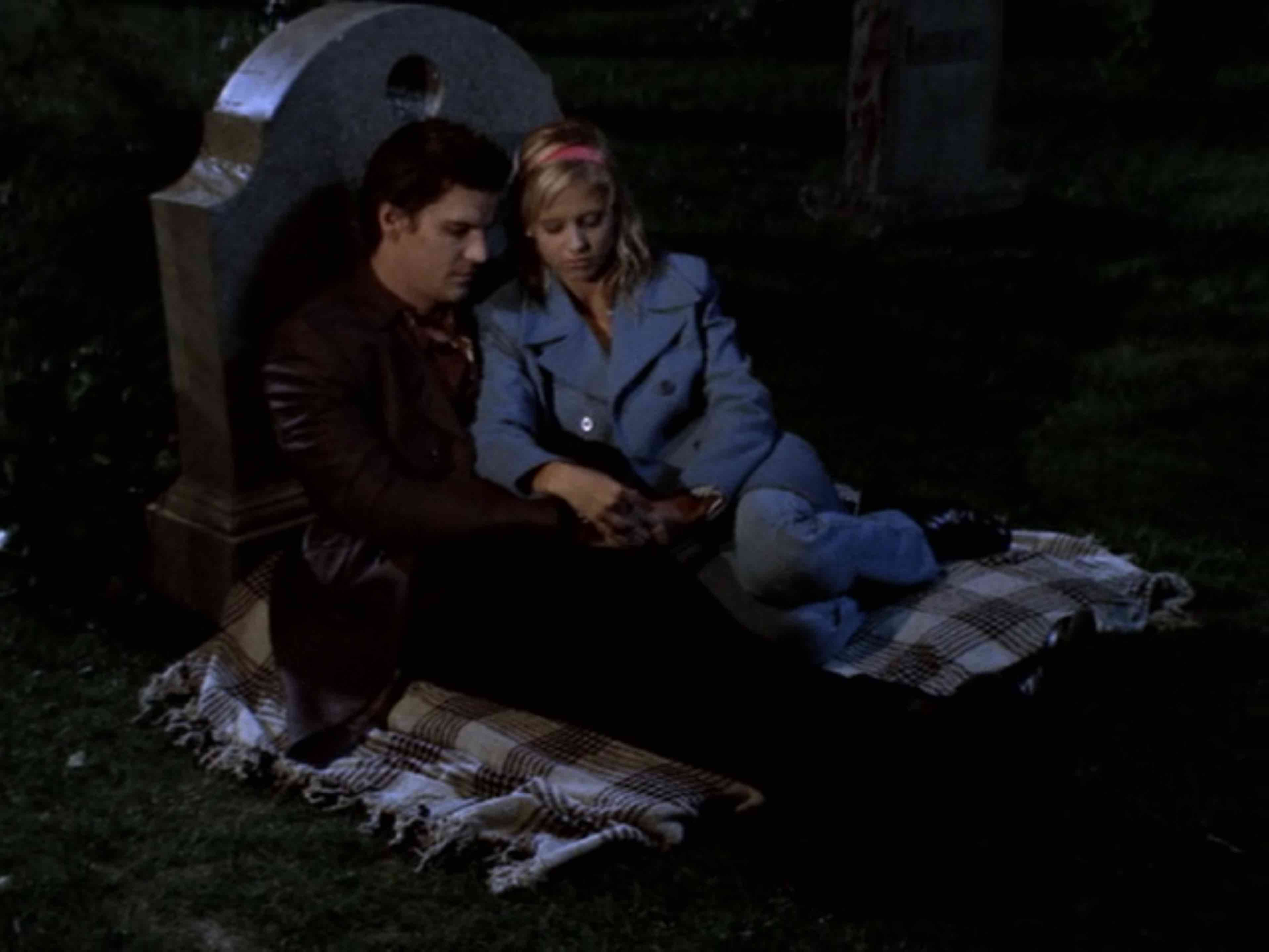 Image description: Buffy and Angel having a picnic at a cemetery.