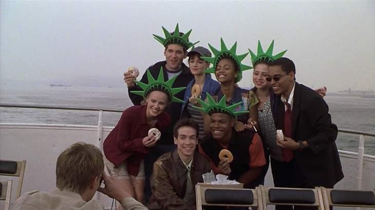 Image description: Eight people, most in Statue of Liberty hats and holding donuts, pose for a picture on a boat.
