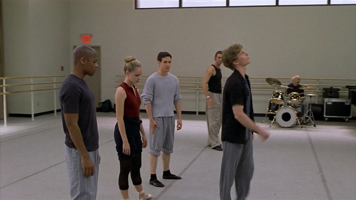 Image description: Jody, Erik, and Charlie stand behind Cooper in a ballet studio.