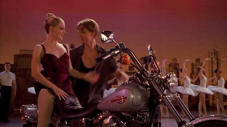 Image description: Onstage, Jody sits on motorcycle, Cooper next to her. Ballet dancers in the background.