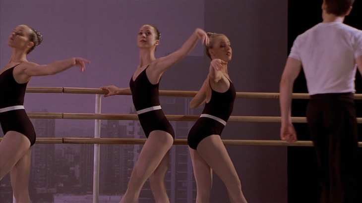 Image description: Jody stands at the barre facing the wrong direction opposite of two other dancers.