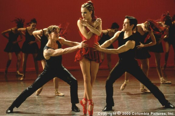 Image description: Jody in a red tutu, dancing on pointe between Charlie and Cooper.