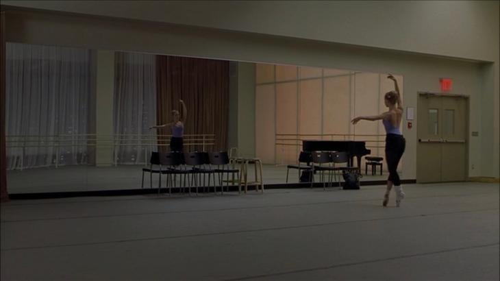 Image description: empty ballet studio where Jody stands in front of the mirror on pointe, alone.