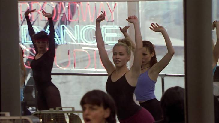 Image description: Jody and two other girls dance, arms in the air.