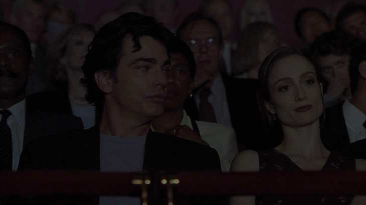 Image description: Jonathan and Kathleen in the audience, Jonathan looking at Kathleen with eyebrows raised and Kathleen staring straight ahead