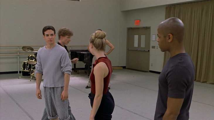 Image description: Charlie in a ballet studio, making a smirk at Jody and Erik.