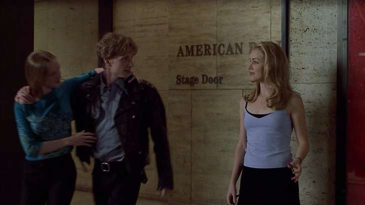 Image description: Jody stands in front of a stage door, Cooper next to her with his arm around a young woman.