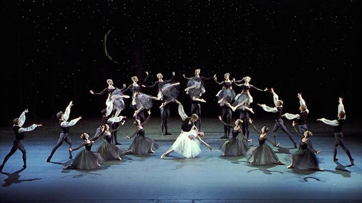 Image description: Onstage, many people dance with starlight in the background