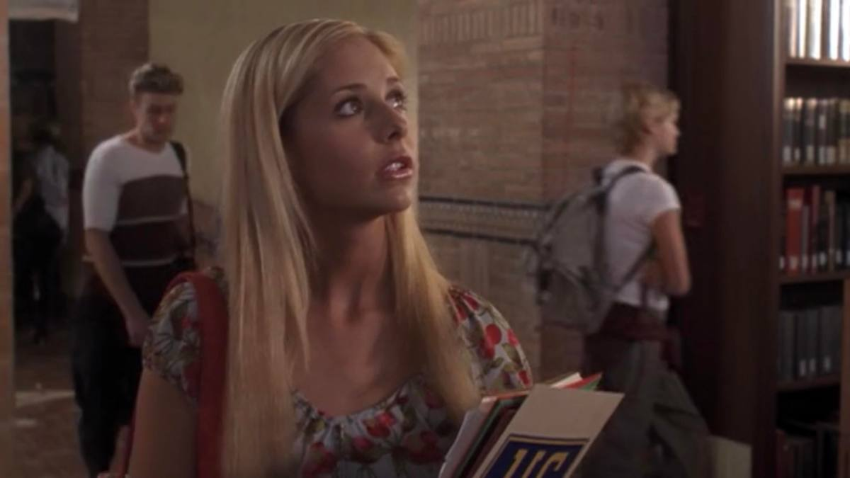 Buffy holds a book and looks around.